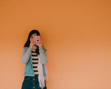 canva-woman-in-blue-jacket-holding-pink-fujifilm-instax-camera-MADGyUj6mLs